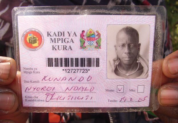 STATE & SOCIETY. Maasai man holding his voter registration card (Askew)