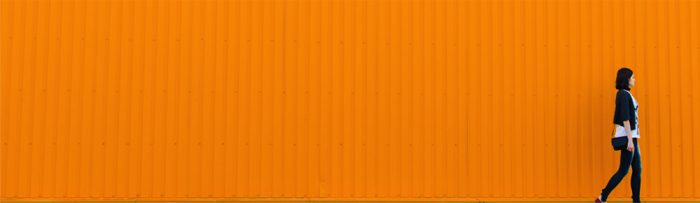 Woman walking in front of a corrugated orange wall