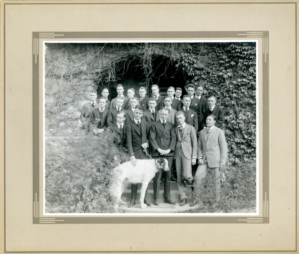 Group portrait of about 20 young men in formal attire under ivy-covered arch, early 1900s.