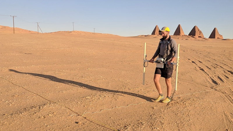 Man walking in desert with scientific equipment, pyramids in background