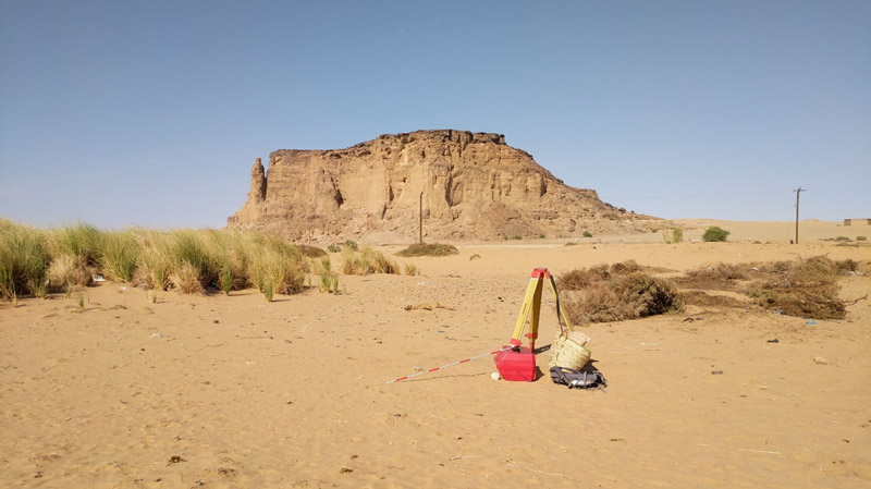 scientific equipment at base of rock outcrop in desert.