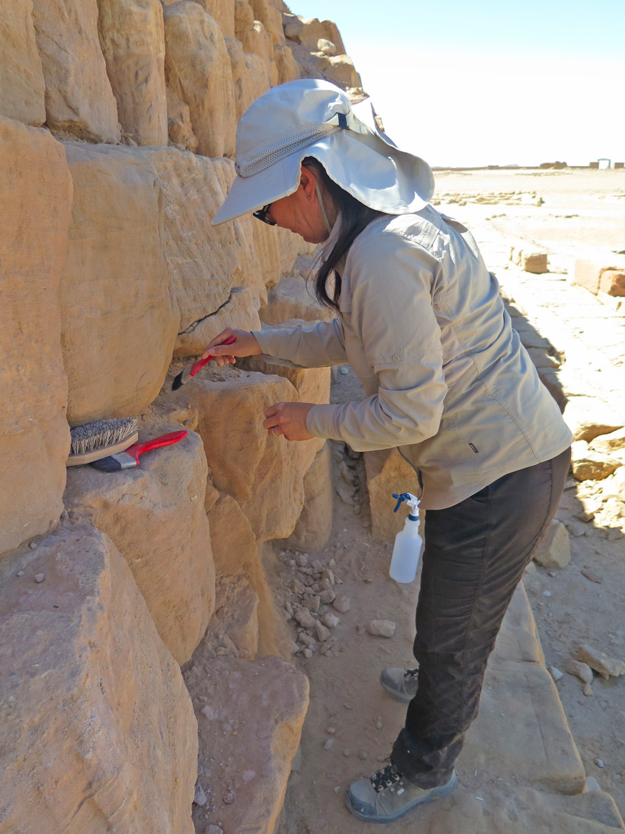 Woman brushing stone blocks of pyramid