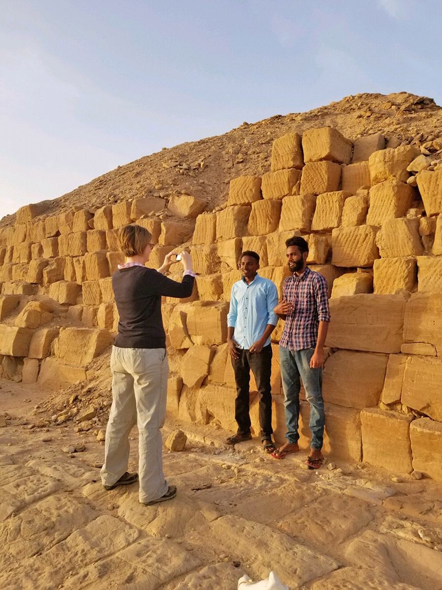Three people at base of ruined pyramid