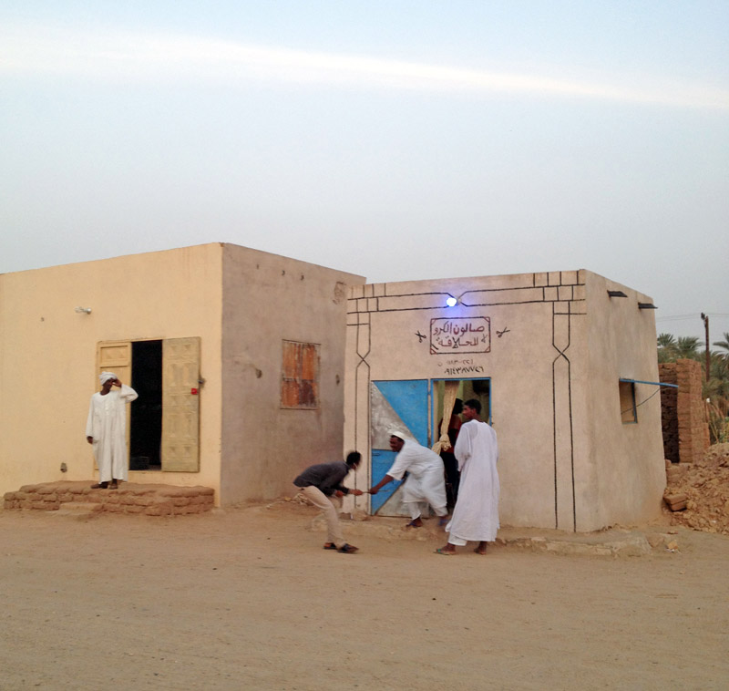 men in front of a low beige building in Sudan