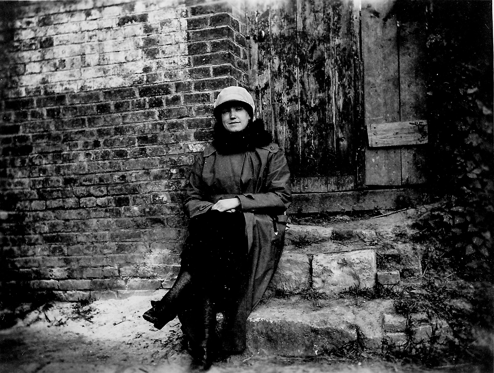 black and white photo of a woman seated on stone steps