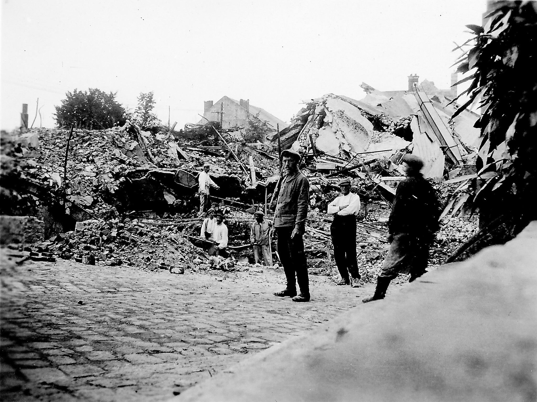 black and white photo of people in front of bombed buildings