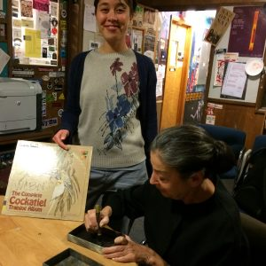 the artist signs her photobook and the engineer, Liz, smiles while holding a record album The Cocktiel