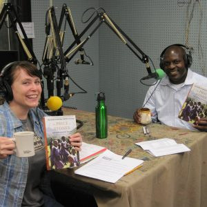Jackson Kaguri at the mic at the studio table with T in headphones, both holding up his book