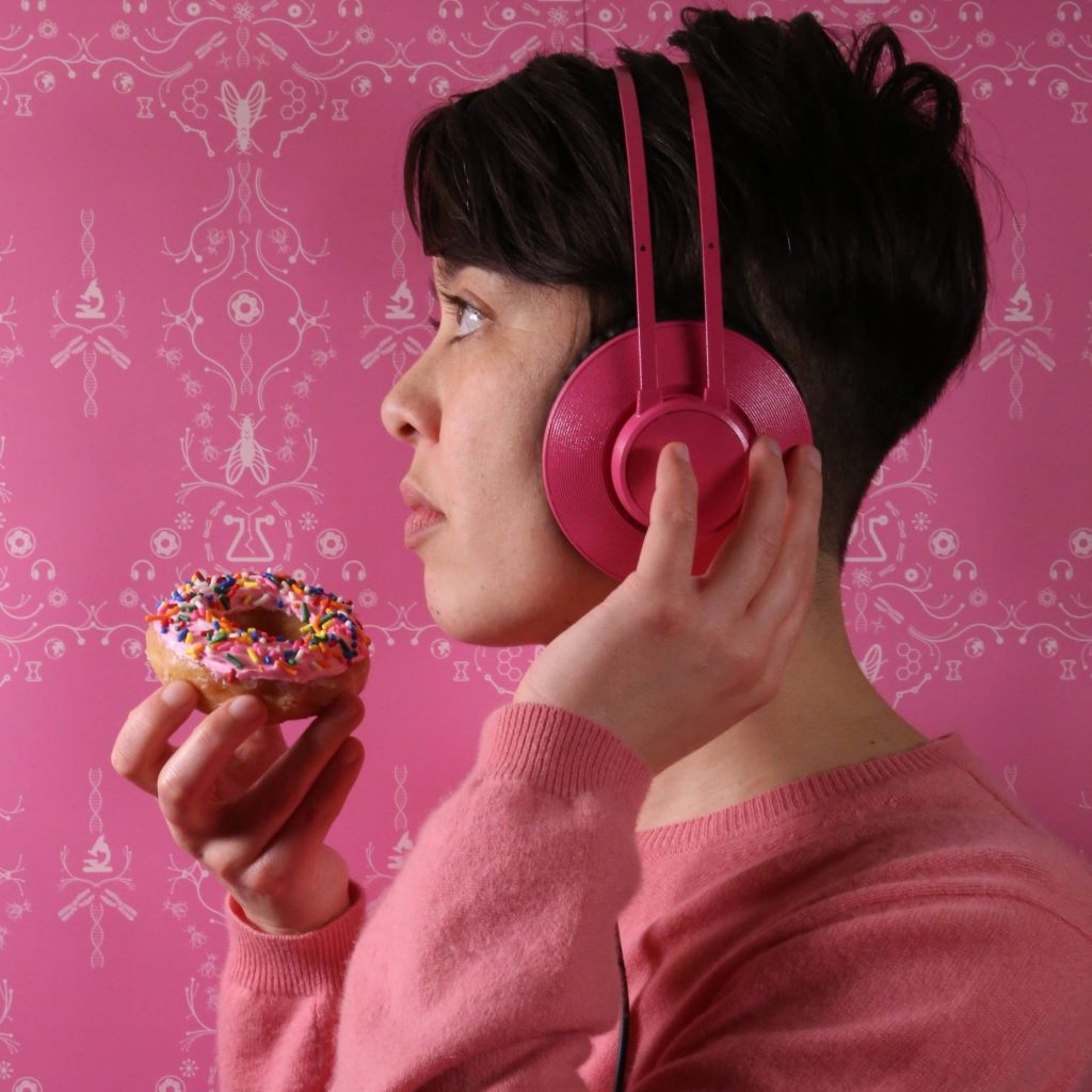 The writer wears headphones and holds a pink donut with sprinkles