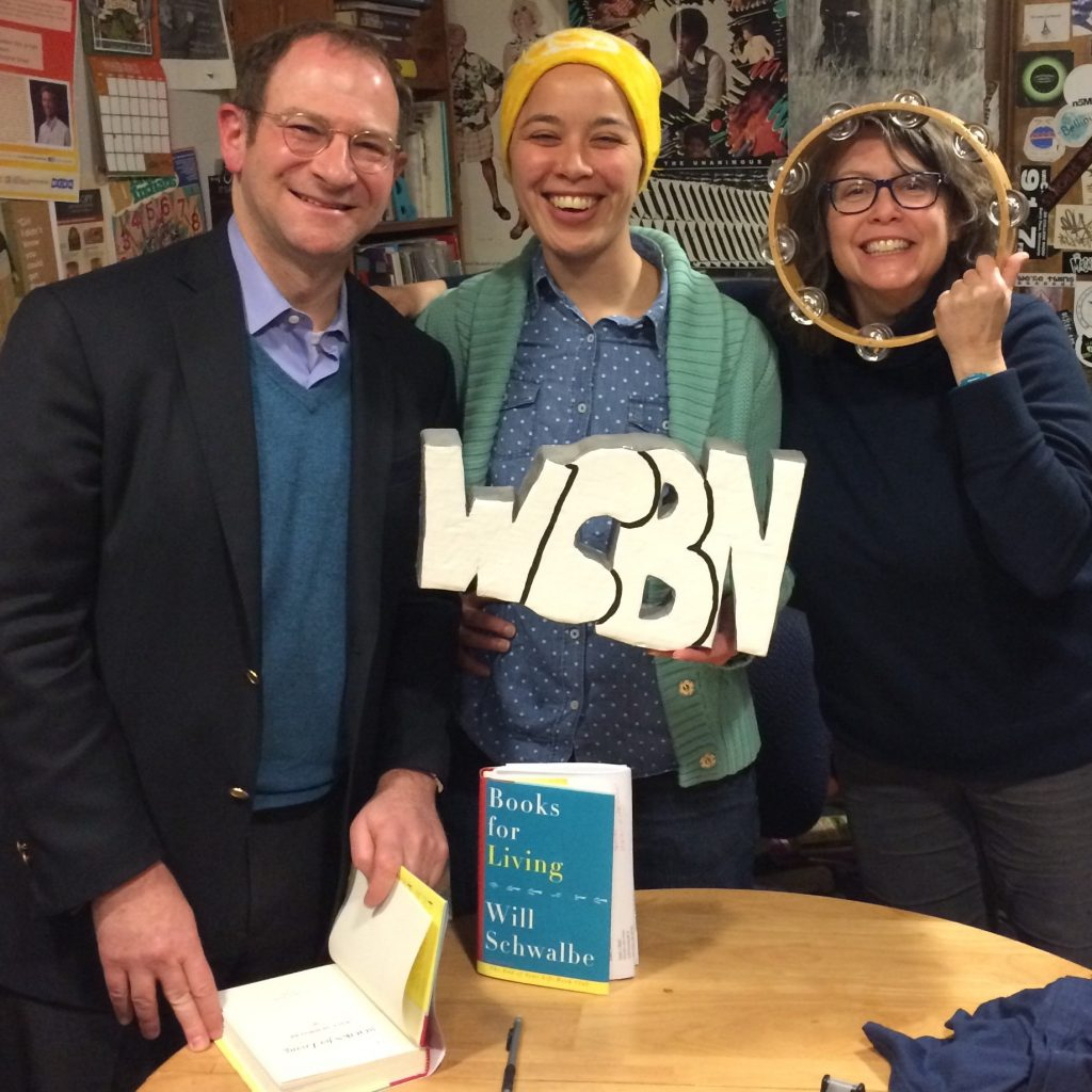 author photo with the Liz holding the WCBN sign and T with her face smiling through a tamborine