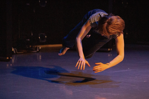 Teresa Fellion during a dance performance hovering above the ground with arms outstretched to form a circle.