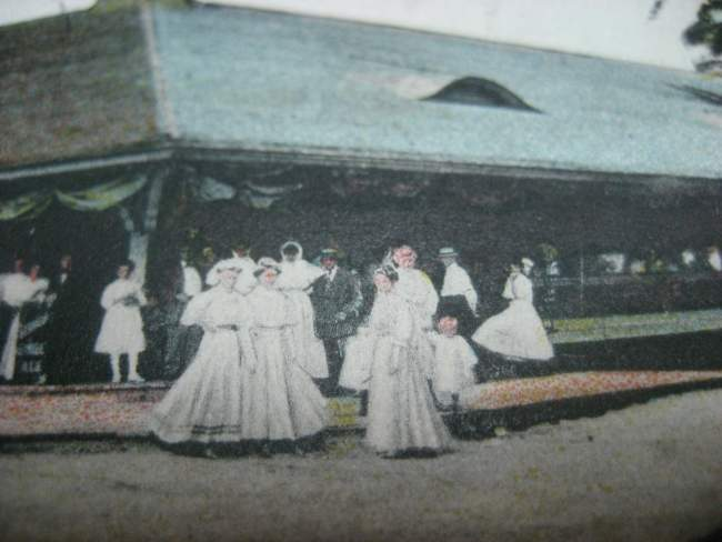 Painting of women in long white dresses with children and some men in suits outside a pavilion.