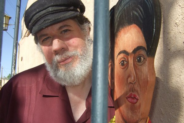 Martin Espada standing next to a mural of Frida Kahlo.