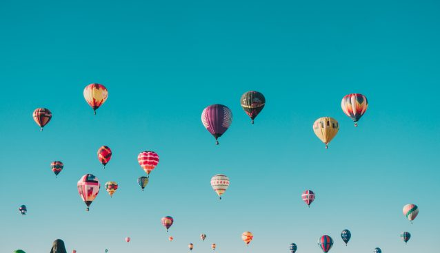Dozens of hot air balloons rising into a clear sky.