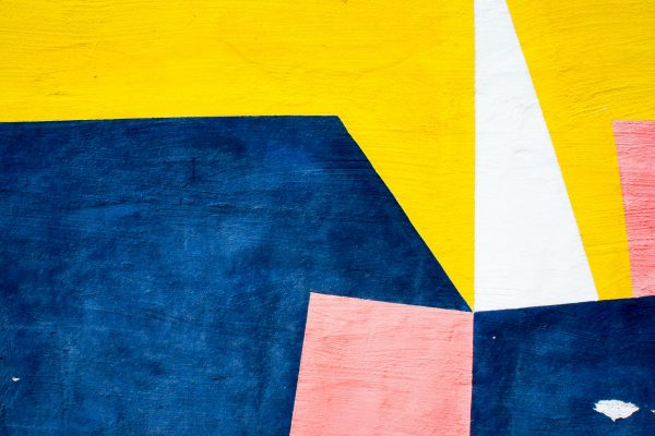 Abstract painting with different shapes in blue, pink, yellow, and white.