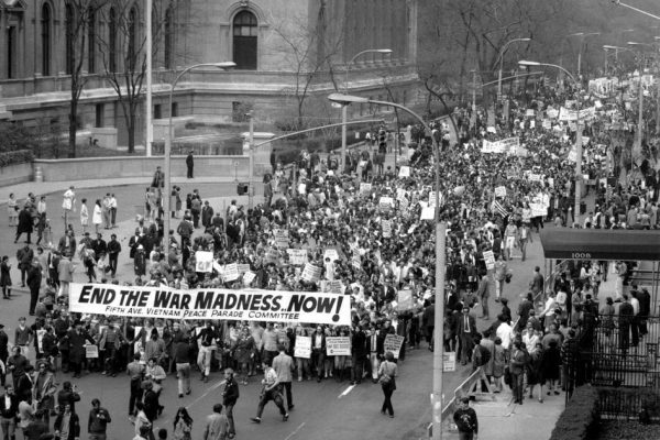 "A street flooded with people protesting the Vietnam War, holding a sign that reads ""end the war madness now!"""