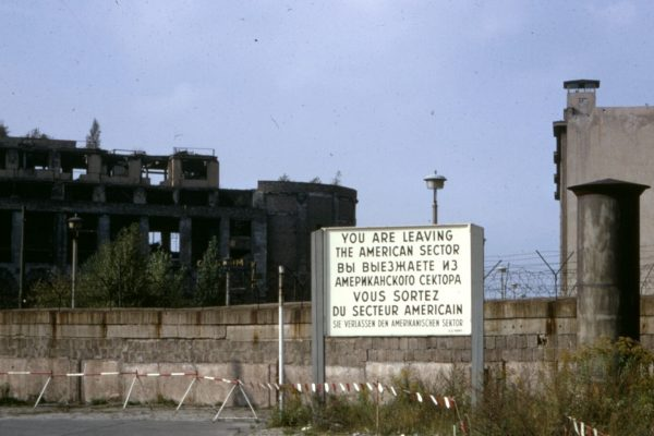 "Sign reading ""you are leaving the American sector"" stands outside of Checkpoint Charlie, with abandoned industrial buildings in the background."