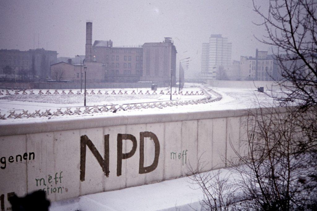 "The Berlin Wall on a snowy day with ""NPD"" graffiti written on it."