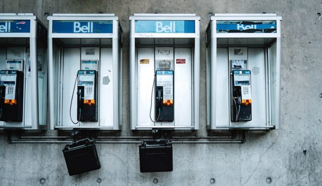Three Bell phone booths against a concrete wall