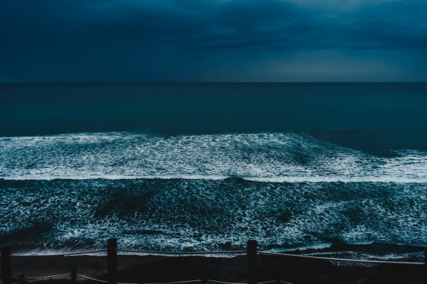Ocean from shore under dark sky
