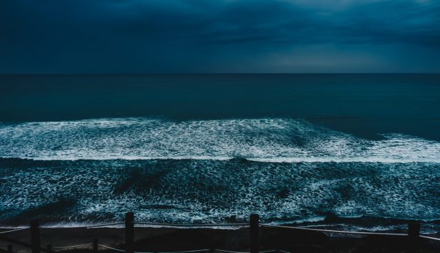Ocean from shore under dark sky