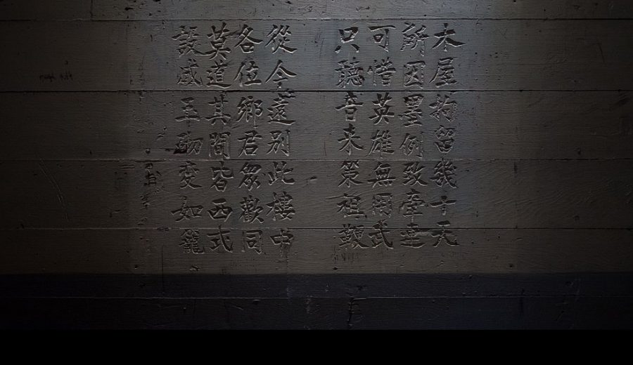 Chinese calligraphy carved into a painted wooden wall