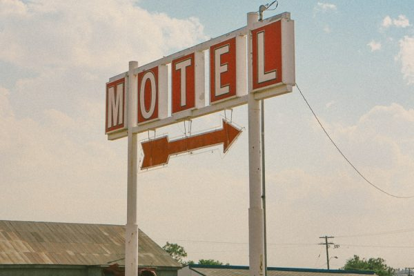 A motel sign with a red arrow against a faded blue sky