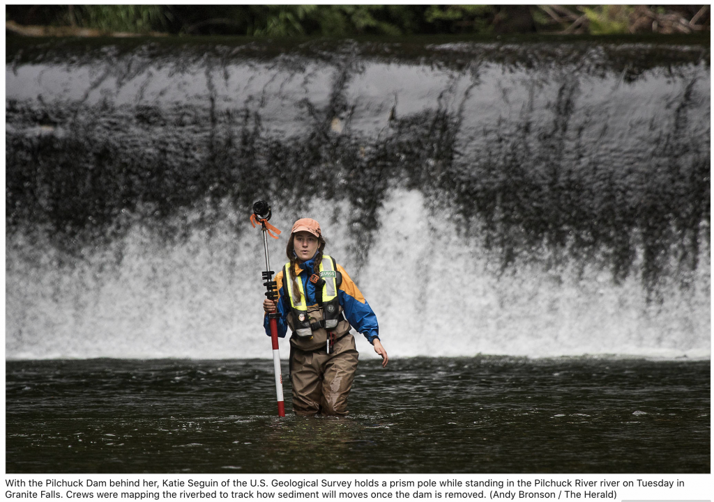 Katie stands in the Pilchuk River in WA, in waders, with temperature monitoring equipment. The dam is behind her.