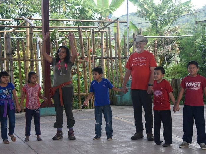 Ivette Perfecto (arms raised) and John Vandermeer play an ecological game with the children during Ecodía. Image credit this page: Jonno Morris.